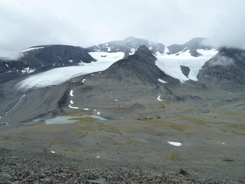 Storslagen vy tillbaka ner i Tarfala med den krympan Storglaciären till vänster och isfallsglaciären till höger. I mitten sticker Nordtoppen fram i molnen.